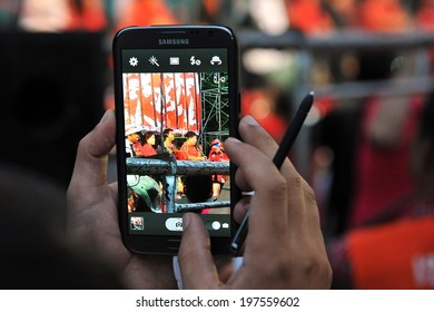 BANGKOK - JAN 29: A protester uses a phablet device to capture a city centre red-shirt rally on Jan 29, 2013 in Bangkok, Thailand. Protesters gathered to demand political prisoners be freed.