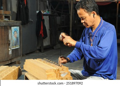 BANGKOK - JAN 5: A master carpenter works at Wat Pho temple on Jan 5, 2011 in Bangkok, Thailand. The temple has a team of artisans to maintain and preserve its Buddhist artwork and structures.