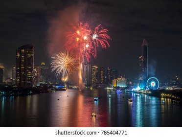BANGKOK - JANUARY 1 : New Year celebration fireworks show over Chaophraya river with surrounding skyscraper buildings in Bangkok, Thailand, on January 1, 2018. And have some smoke artifact.