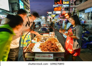 BANGKOK - January 24,2016: A street vendor sells fried cockroaches and other insects to tourists on Khao San Road in Bangkok, Thailand. There is 16,000 registered street vendors in Bangkok.