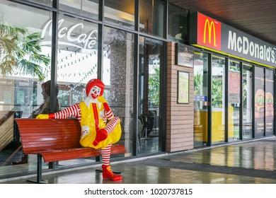 BANGKOK - JANUARY 9, 2018 : ronald-mcdonald , Mc donald's mascot , on bench in front of  McDonald's restaurant and cafe