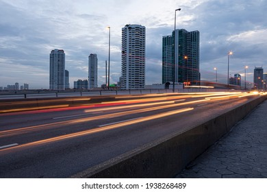 Bangkok, July 18, 2011: View of light trails and motion blur of vehicles on a highway road against the backdrop of the city skyline of Bangkok.