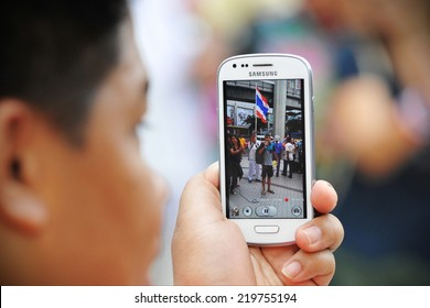 BANGKOK - JULY 21: A protester uses a smartphone to video an anti-government rally on July 21, 2013 in Bangkok, Thailand. The protesters are calling for the government to be overthrown.