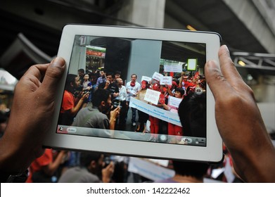 BANGKOK - JUN 2: A protester uses a tablet computer to capture a Red Shirt rally in Bangkok's shopping area on Jun 2, 2013 in Bangkok, Thailand. Protesters rallied to show support to the government.