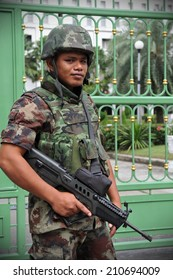 BANGKOK - JUN 26: An unidentified armed Thai soldiers stands guard outside a military installation as anti election protesters hold a rally nearby on Jun 26, 2011 in Bangkok, Thailand.