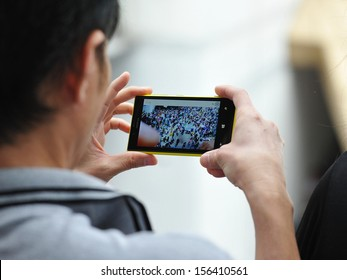 BANGKOK - JUN 30: A passerby uses a smartphone to capture an anti-government rally on Jun 30, 2013 in Bangkok, Thailand. The protesters known as V for Thailand call for the government to be removed.