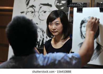 BANGKOK - JUN 30: An unidentified woman is sketched by an artist at the Bangkok Art and Cultural Centre (BACC) on Jun 30, 2013 in Bangkok, Thailand. Opened in 2010 BACC is home to many art studios.