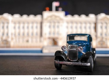 BANGKOK - JUNE 11, 2016 : Vintage Blue Car Miniature in front of abstract blur of old palace made from paper. Classic Retro Car. Selective focus. Closed up and Macro