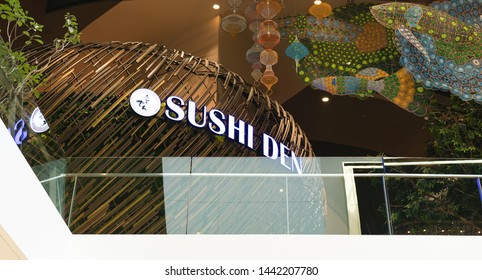 BANGKOK - JUNE 22, 2019: View looking up from a lower floor of the logo of the Sushi Den japanese restaurant inside the popular Icon Siam shopping mall