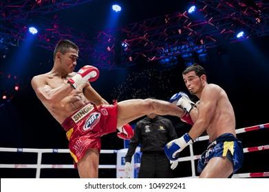 "BANGKOK - JUNE 9: Muay Thai Super Lightweight World Championship - Jomtong Chuwattana (Thailand) kicking Yetkin Ozkul (Turkey) at ""BATTLE FOR THE BELTS"" event on June 9, 2012 in Bangkok, Thailand"