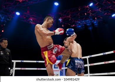"BANGKOK - JUNE 9: Muay Thai Super Lightweight World Championship - Jomtong Chuwattana (TH) kicking Yetkin Ozkul (Turkey) in his liver at ""BATTLE FOR THE BELTS"" on June 9, 2012 in Bangkok, Thailand"