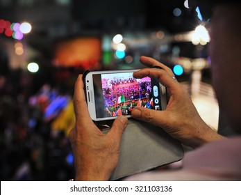BANGKOK - MAR 19: A passerby uses a smartphone to capture a Thai boxing match on a city centre street on Mar 19, 2013 in Bangkok, Thailand. Thailand has one of the world's highest uses of Istagram.