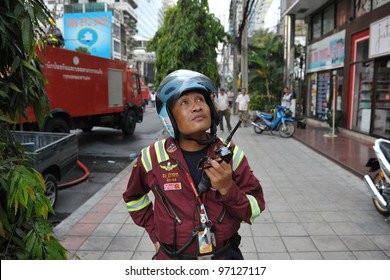 BANGKOK - MAR 5: A firefighter looks on at blaze at Fico Building on Asoke Road in the city centre on Mar 5, 2012 in Bangkok, Thailand. The BMA has launched an investigation in the cause of the blaze.