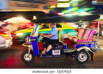 """BANGKOK - MARCH 03: Tuk - tuk on Chinatown street at night on March 03, 2013 in Bangkok.  There are more than 100,000 """"tuk-tuk"""" in Bangkok."""