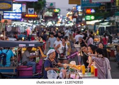 BANGKOK, MARCH 11: Tourists haggle with a Pad Thai vendor on Bangkok's Khao San Road on March 11, 2018.