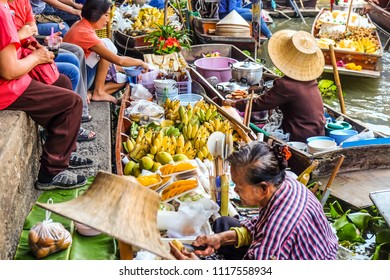 BANGKOK – MARCH 18: People shopping food from wooden boats at Amphawa floating market on March 18, 2018 in Bangkok. Traditional popular place buying and selling Souvenir in Amphawa canals of Thailand.
