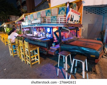 BANGKOK - MARCH 9, 2015: A local man sits at a fancy bar made of an old car in the Khao San Road area, the center of the backpackers universe.