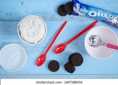 Bangkok - May 26, 2019 : Top view of Diary Queen ice cream in a take home cup (blizzard Oreo flavor), Oreo cookies, plastic spoons and stainless steel ice cream scoop. DQ is successful ice cream chain