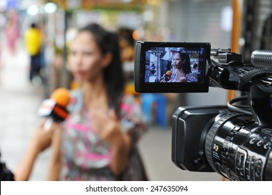 BANGKOK - MAY 27: A bystander gives an interview to news media after a nail bomb blast on May 27, 2013 in Bangkok, Thailand. The bomb injured 7 people, while police unclear of a motive or suspects.