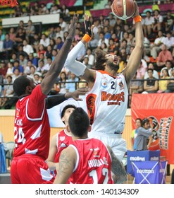 """BANGKOK - MAY 28:Christien Charles #21 rebound ball compete with Justin Williams #27 in an ASEAN Basketball League """"ABL"""" playoffs game3 at Nimibut Stadium on May 28, 2013 in Bangkok,Thailand."""