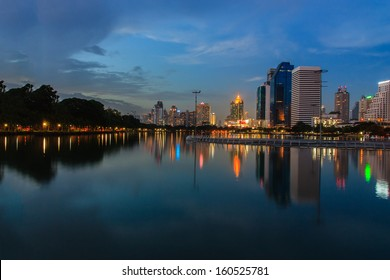Bangkok at night with lights shining down from commercial building reflected on the surface of the water in a park in Bangkok, Thailand.