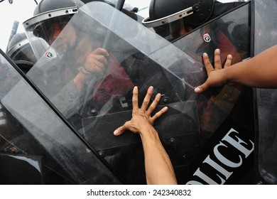 BANGKOK - NOV 24: Anti government protesters push shields of riot police during a violent a large rally on Nov 24, 2012 in Bangkok, Thailand. Protesters call for the government to be overthrown.
