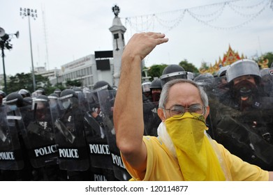 BANGKOK - NOV 24: A nationalist protester from Pitak Siam beckons to other protesters to confront riot police while attending a large anti-government rally on Nov 24, 2012 in Bangkok, Thailand.
