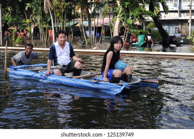 BANGKOK - NOV 4: City residents navigate a flooded street by boat as tens of thousands evacuate their homes in the worst flooding in over 50 years on Nov 4, 2011 in Bangkok, Thailand.