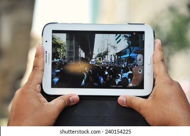 BANGKOK - NOV 4: A protester uses a tablet device to capture an anti-government rally in the Thai capital's central business district on Nov 4, 2013 in Bangkok, Thailand.