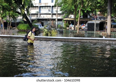 BANGKOK - NOV 4: An unidentified woman wades through a flooded street in the Thai captial on Nov 4, 2011 in Bangkok, Thailand. Approximately a fifth of the Thai capital is submerged under floodwater.