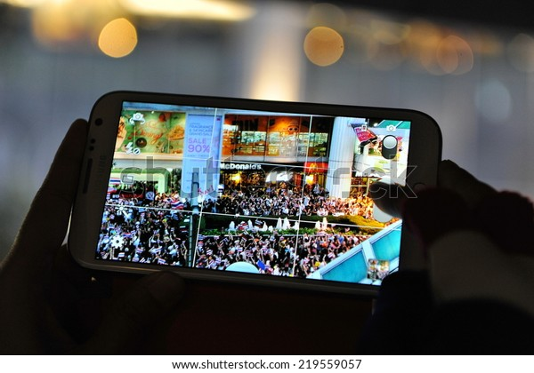BANGKOK - NOV 7: A protester uses a smartphone to capture an anti-government rally on Nov 7, 2013 in Bangkok, Thailand. The Thai protest movement are calling for the government to be overthrown.