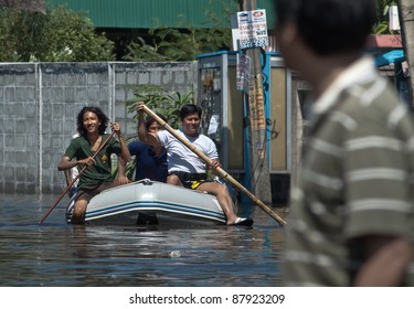 BANGKOK - NOVEMBER 1: A group of people sail a boat to evacuate from the flooded area in the Rama - Indra road during the massive flood crisis on November 1, 2011 in Bangkok.