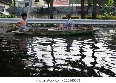 BANGKOK - NOVEMBER 4: Unidentified people use a boat on a flooded section of road in Pinklao district on November 4, 2011 in Bangkok, Thailand. Thailand is facing its worst floods in over 50 years.