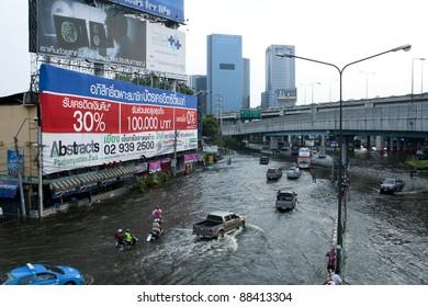 BANGKOK - NOVEMBER 5: Cars navigate through the flood on Phahonyothin Road during the worst flooding in Bangkok, Thailand on November 5, 2011.