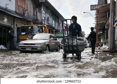 BANGKOK - OCT 26: People make their way along a flooded street in Chinatown after the Chao Phraya River bursts its banks in the worst flooding in decades on Oct 26, 2011 in Bangkok, Thailand.