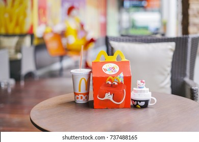 BANGKOK - OCTOBER 10 : Happy meal set and toy,in soft focus, with blurred Ronald Mcdonald at McDonald's restaurant on October 10, 2017 in Bangkok, Thailand