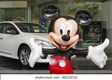 BANGKOK - SEPT 10, 2016 : Mickey Mouse giant fiberglass mascot (scale in human size) is standing to welcome visitor in front of Nisson Showroom. Mickey Mouse is most successful Disney character.