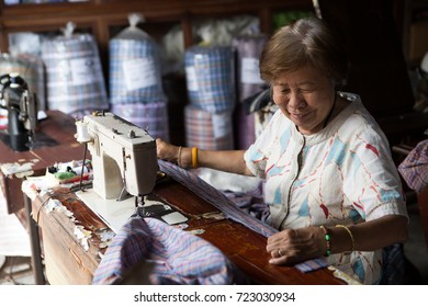 BANGKOK - SEPTEMBER 11: An unidentified woman operates a sewing machine in a garments factory on Sep 11, 2017 in Bangkok, Thailand. Textile and clothing is Thailand's largest manufacturing industry.