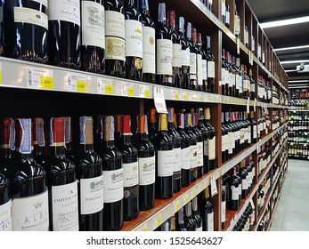 Bangkok, TH - AUGUST 19, 2019: Perspective viewing of various import wines and alcohol liquors sale on the wooden shelf in a supermarket.