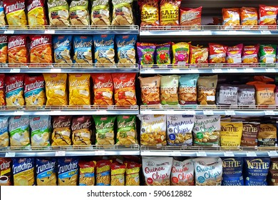 Bangkok, TH - FEBRUARY 14, 2017: Potato chips and snack foods in supermarket shelf that are the cause of an increase fat person.