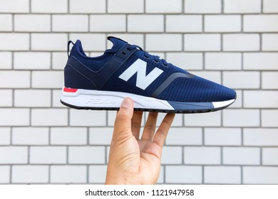 BANGKOK, THAIAND - JUNE 2, 2018:Hand holding New balance shoes model MRL247DH blue color on brick wall background.