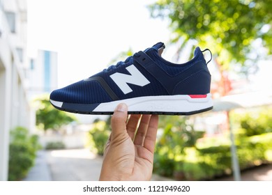 BANGKOK, THAIAND - JUNE 2, 2018:Hand holding New balance shoes model MRL247DH blue color on nature background.