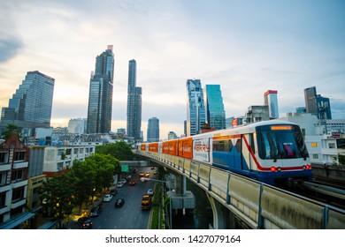 BANGKOK, THAILAND - 02 JUN 2019 - BTS sky train runs through the station. View of Bangkok skyline and skyscraper with BTS skytrain.