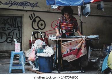 BANGKOK, THAILAND - 04 JUNE, 2019 : Unidentified woman sewing in a small tailor shop at Saphan Hua Chang Pier in Bangkok, Thailand.