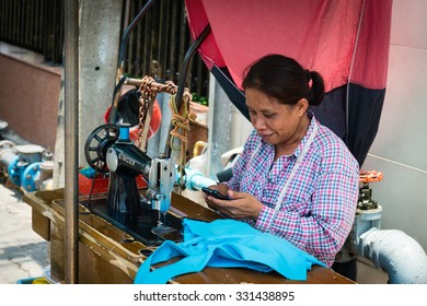 BANGKOK, THAILAND - 07 MAY 2014: Female street seamstress with old sewing machine on wooden bench using her phone.