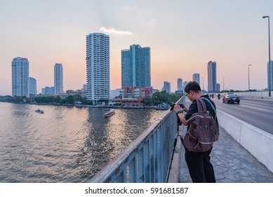 BANGKOK, THAILAND - 1 March 2017 : Tourist takes photos of the view from Taksin Bridge of Sathon District. Below the bridge the Sathorn pier offers the service of Chao Phraya Express boats and ferry.