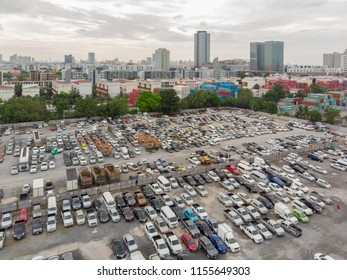 Bangkok Thailand 10July2018 : Aerial view over huge outdoor parking lots with many used vehicles and high building of Bangkok city in background. Shot by 4K resolution drone.