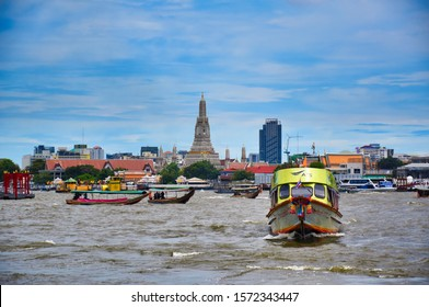 Bangkok, Thailand .11.24.2019: Cityscape view of Bangkok with motor boats, long tailed boats, traditional wooden boats on the Chao Phraya River with the famous and amazing Wat Arun in the background