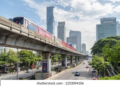 Bangkok, Thailand - 14 October, 2018: Amazing cityscape. Skytrain passing above Sathon Road. Viaduct of BTS Silom Line. MahaNakhon Tower is visible on blue sky background.