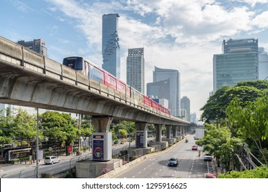 Bangkok, Thailand - 14 October, 2018: Skytrain passing above Sathon Road. Viaduct of BTS Silom Line. MahaNakhon Tower is visible on blue sky background. Amazing cityscape.